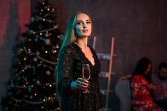 Belle jeune femme avec le verre de champagne à la fête de Noël Photos stock