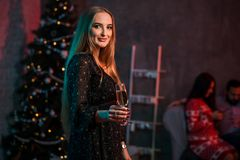 Belle jeune femme avec le verre de champagne à la fête de Noël Image libre de droits