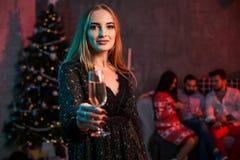 Belle jeune femme avec le verre de champagne à la fête de Noël Photo libre de droits