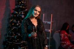 Belle jeune femme avec le verre de champagne à la fête de Noël Image stock