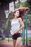 Belle jeune femme avec les cheveux de flottement jouant le basket-ball dehors Photographie stock