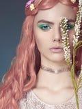 Belle jeune femme avec les cheveux et les fleurs roses Image stock