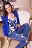 Belle jeune femme avec les cheveux foncés dans la veste et des jeans élégants Image libre de droits