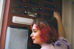 Belle jeune femme avec les cheveux oranges sonnant la porte d'un appartement photographie stock libre de droits