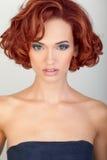 Belle jeune femme avec les cheveux rouges Image stock