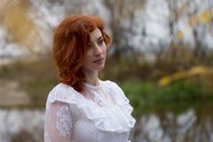 Belle jeune femme avec les cheveux rouges dehors en automne Images stock