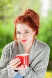 Belle jeune femme avec les cheveux rouges se reposant dans le jardin, détendant, café potable images libres de droits