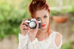 Belle jeune femme avec les cheveux rouges se reposant dans le jardin prenant des photos avec l'appareil-photo photo libre de droits