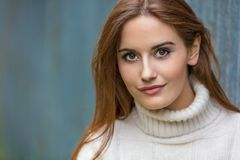 Belle jeune femme avec les cheveux rouges utilisant un chandail Photographie stock libre de droits