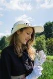 Belle jeune femme avec les gants et la fleur blancs photographie stock
