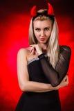 Belle jeune femme avec les klaxons rouges de démon Photographie stock