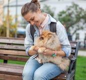 Belle jeune femme avec son chiot de Pomeranian sur ses mains dessus Photographie stock