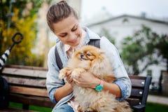 Belle jeune femme avec son chiot de Pomeranian sur ses mains dessus Images stock