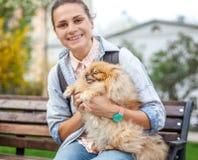 Belle jeune femme avec son chiot de Pomeranian sur ses mains dessus Photos stock