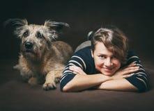 Belle jeune femme avec un chien hirsute drôle sur un backgrou foncé Photographie stock