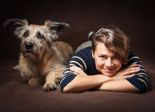 Belle jeune femme avec un chien hirsute drôle sur un backgrou foncé Photo libre de droits