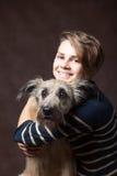 Belle jeune femme avec un chien hirsute drôle sur un backgrou foncé Image stock