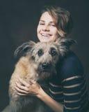 Belle jeune femme avec un chien hirsute drôle sur un backgrou foncé Photos stock