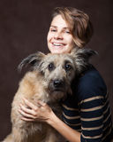 Belle jeune femme avec un chien hirsute drôle sur un backgrou foncé Images stock