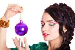 Belle jeune femme avec une babiole pourpre de Noël Photo libre de droits