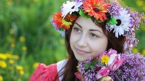Belle jeune femme avec une guirlande sur sa tête et un bouquet de lilas dans des ses mains banque de vidéos