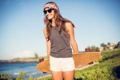 Belle jeune femme avec une planche à roulettes photo stock
