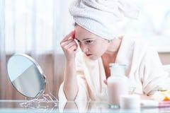 Belle jeune femme avec une serviette sur sa tête regardant sa peau dans un miroir Concept d'hygiène et d'entretenir la peau photo stock