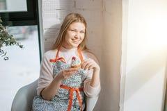 Belle jeune femme ayant le petit gâteau tout en se reposant près de la fenêtre images stock