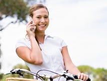 Belle jeune femme blonde avec le vélo en parc parlant au-dessus du téléphone photo libre de droits