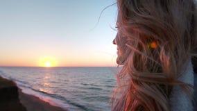Belle jeune femme blonde bouclée caucasienne au lever de soleil ou au coucher du soleil par l'océan Le vent développe les cheveux banque de vidéos