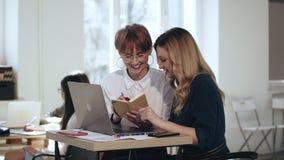 Belle jeune femme blonde de patron travaillant avec l'ordinateur portable, écoutant le collègue avec des notes à la table à la mo banque de vidéos