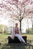 Belle jeune femme blonde en parc de Sakura Cherry Blossom au printemps appr?ciant la nature et le temps libre pendant elle voyage images libres de droits