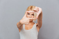 Belle jeune femme blonde faisant le cadre avec des doigts Photos libres de droits