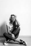 Belle jeune femme blonde posant sur le plancher. style de denim de jeans photographie stock libre de droits