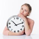Belle jeune femme blonde sereine embrassant une horloge Images stock