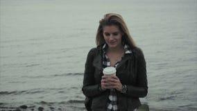 Belle jeune femme blonde tenant une tasse de café dans des ses mains près de la mer banque de vidéos