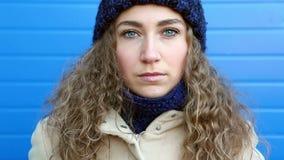 Belle jeune femme bouclée triste, avec des yeux bleus se penchant contre le mur bleu clips vidéos