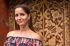 Belle jeune femme bronzée posant sur la caméra contre un mur modelé images stock