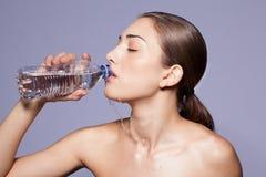 Belle jeune femme buvant d'une bouteille de l'eau Image stock