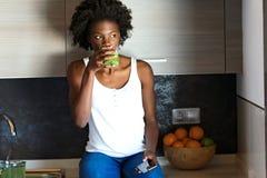 Belle jeune femme buvant du jus vert de detox et à l'aide de son téléphone portable à la maison photo stock