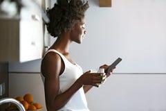 Belle jeune femme buvant du jus vert de detox et à l'aide de son téléphone portable à la maison photos libres de droits