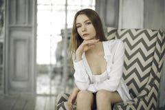 Belle jeune femme calme dans une robe blanche à la maison images libres de droits
