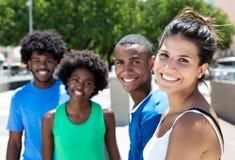 Belle jeune femme caucasienne avec des amis d'afro-américain dans la ville Image libre de droits
