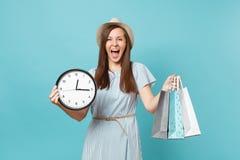 Belle jeune femme caucasienne de portrait dans la robe d'été, chapeau de paille tenant des sacs de paquets avec des achats après  photo stock