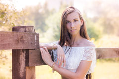 Belle jeune femme châtain à la barrière en bois Photographie stock