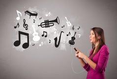 Belle jeune femme chantant et écoutant la musique avec le musica Photographie stock libre de droits