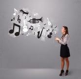 Belle jeune femme chantant et écoutant la musique avec le musica Photographie stock