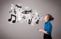 Belle jeune femme chantant et écoutant la musique avec le musica Image stock