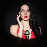 Belle jeune femme chanteuse avec le microphone photographie stock libre de droits