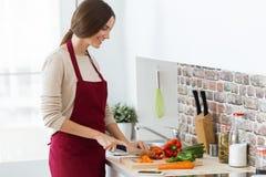 Belle jeune femme coupant les légumes frais dans la cuisine Photos stock